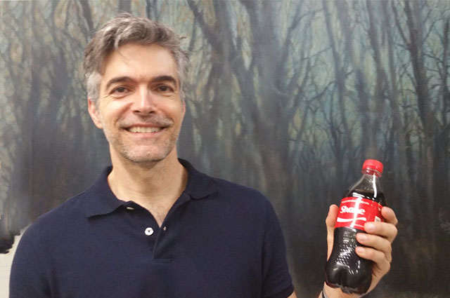 Shane stands with a custom Coke bottle and a smile in front of one of his paintings.
