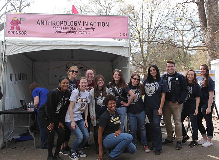 "12 KSU students posing in front of ""Anthropology In Action"" sign and activity tent at Atlanta Science Festival Expo"